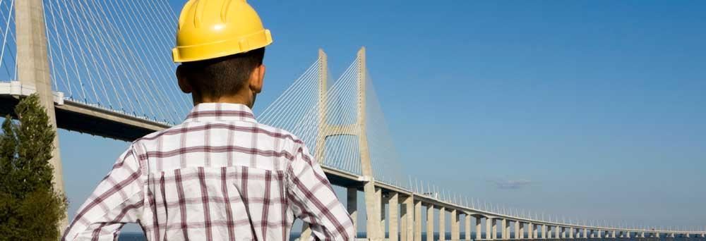 Ingenieur mit gelben Helm schaut auf die Brücke, die über das Wasser geht. Mit einem Link auf die Startseite.